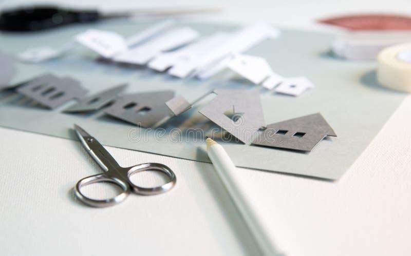 Elementos de projeto cortados em papel com ferramentas: tesoura, faca, pare, cola, etc Criação de uma vista de cidade em curso Cr imagens de stock