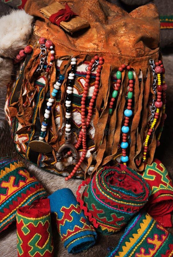 Elementos del paño tradicional del invierno, del bolso de cuero y de telas adornadas ricas de la tribu nómada del círculo del nor foto de archivo libre de regalías