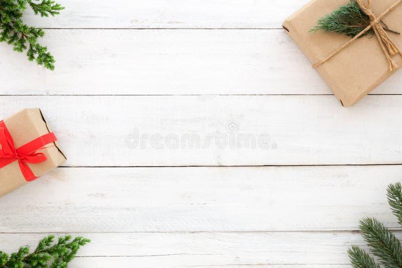 Elementos rústicos da decoração das caixas de presente do presente de Natal e das folhas do abeto no fundo de madeira branco imagens de stock