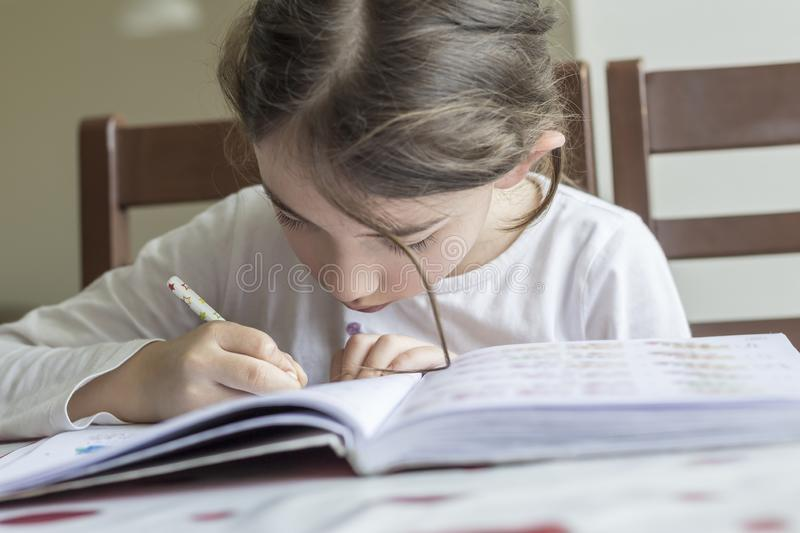The elementry student is making her homework stock photos