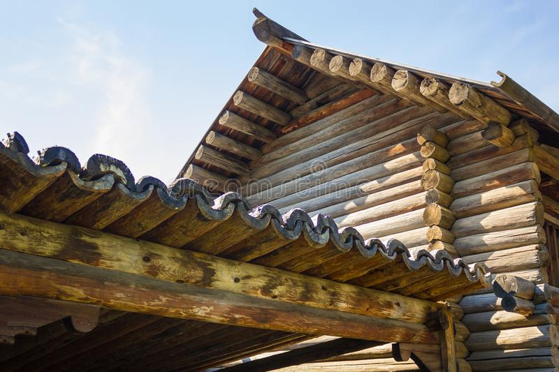 Elements of wooden architecture. An old wooden building made of round wood, handmade, carpentry. Covering the roof with hollow logs. Ancient wooden architecture stock photos