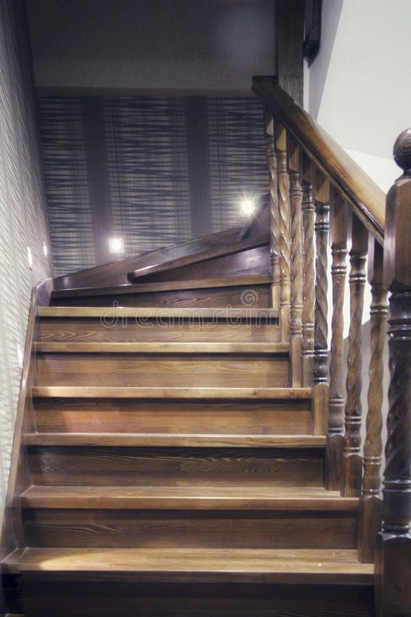 Elements of wooden stairs, with carved handrails. technological stylistic lighting design in a classic interior stock photography
