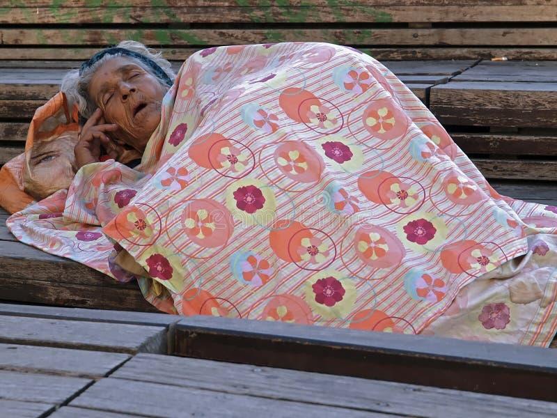 Elemosinando donna che dorme fuori fotografia stock libera da diritti