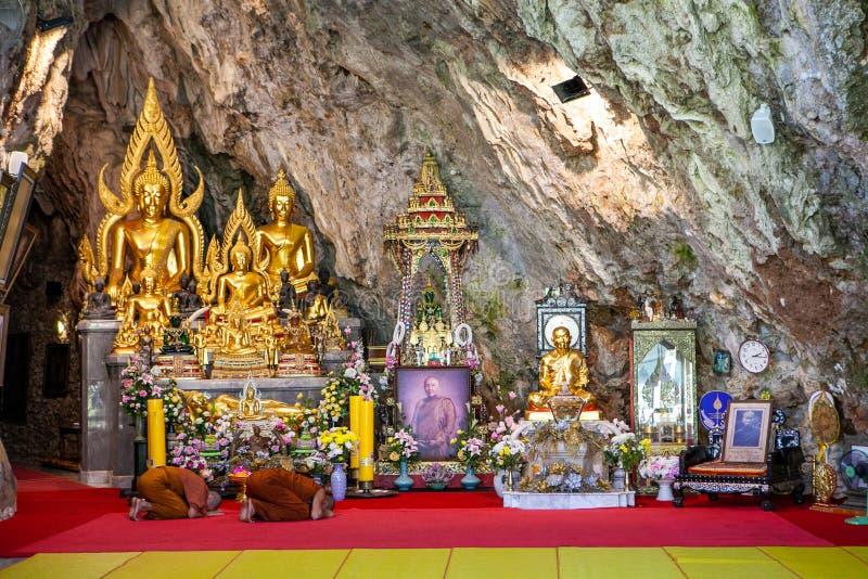 Elemosine cerimoniali e monaci a ginocchioni dentro Wat Tham Pha Plong Temple, Chiang Dao immagine stock