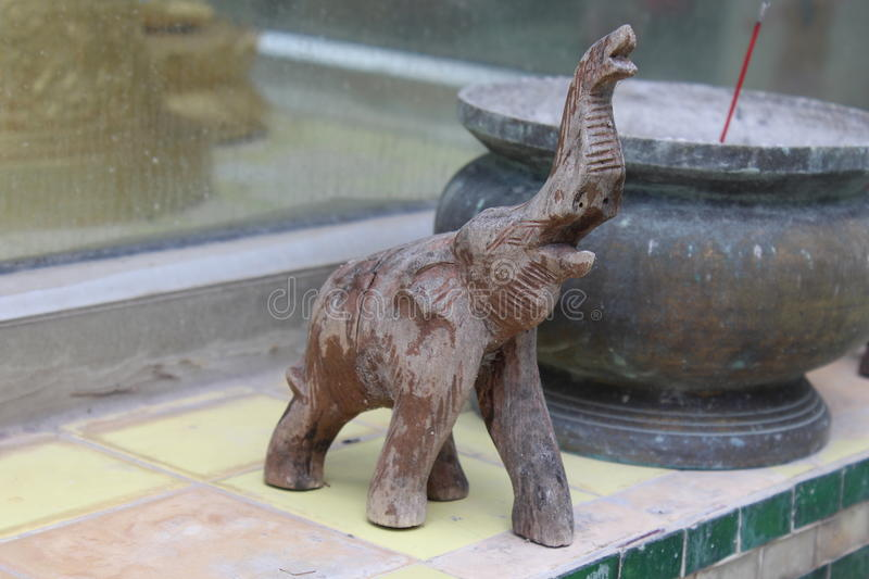 Elephant a Statue. At a Buddhist god alter next to a burning senses bowl a small brown statue of a elephant blows is trunk royalty free stock images