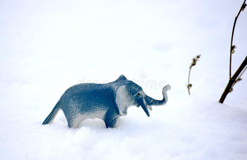Elephant toy figurine on snow, climate change concept. Image stock image
