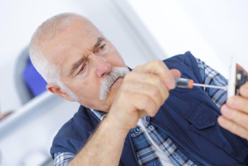 Eletricista adulto superior que verifica e que repara a tomada imagem de stock