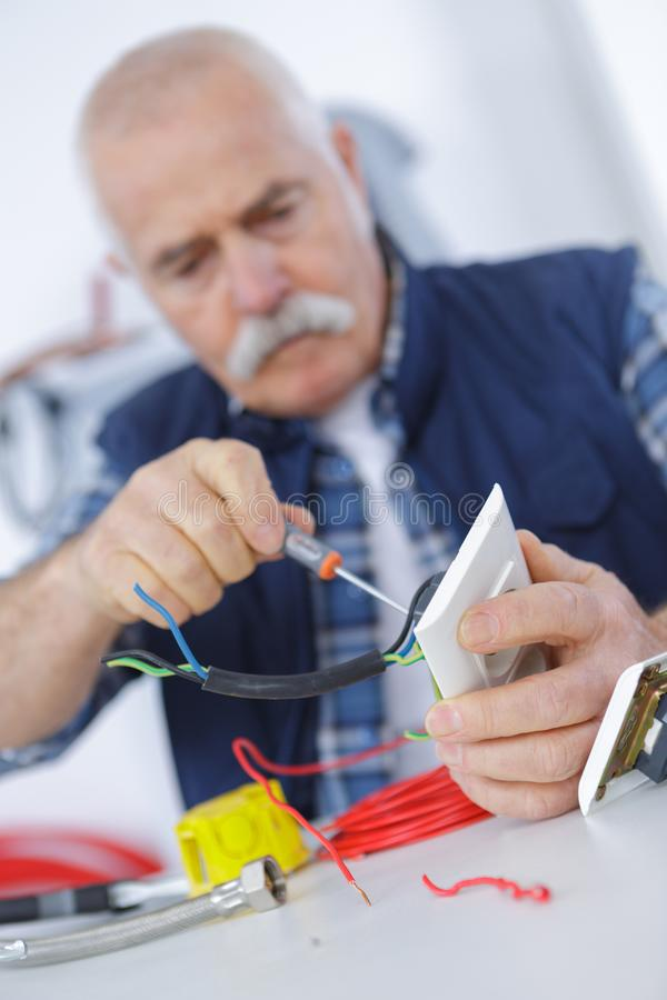 Eletricista adulto superior que verifica e que repara a tomada fotografia de stock royalty free