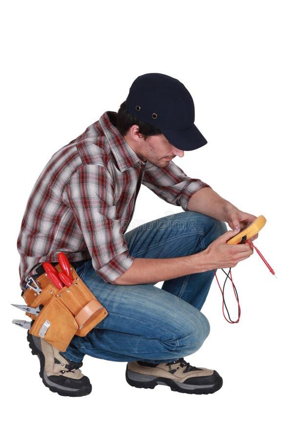 Eletricista ajoelhado com um voltímetro. foto de stock