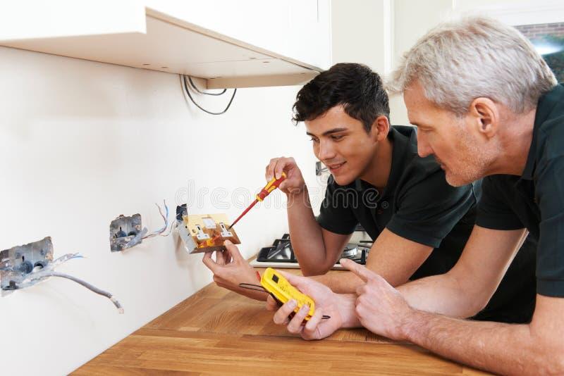 Eletricista With Apprentice Working na casa nova fotos de stock royalty free