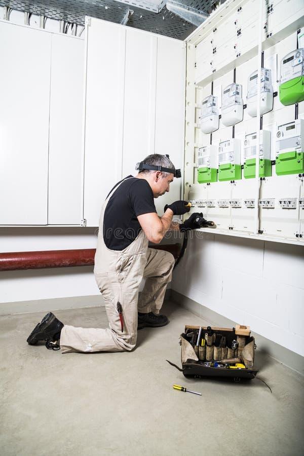Eletricista com a caixa das ferramentas que fixam a caixa do fusível ou a caixa de interruptor imagens de stock