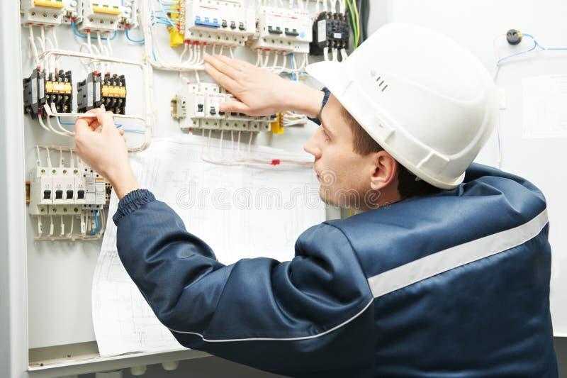 Eletricista com desenhar na caixa da linha eléctrica foto de stock