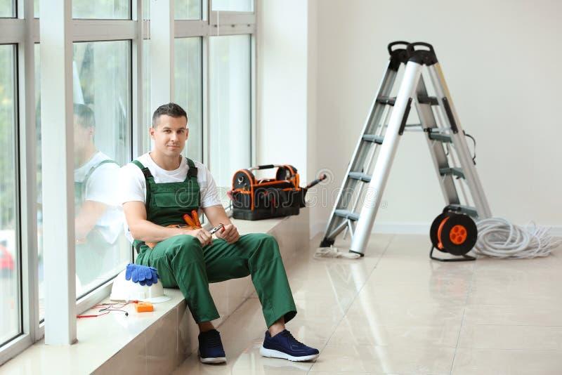 Eletricista com os alicates e o cabo que sentam-se na soleira no apartamento novo fotos de stock royalty free