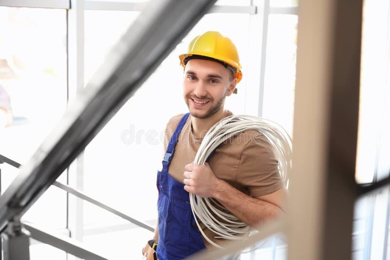 Eletricista de sorriso novo que guarda o grupo dos fios imagem de stock royalty free