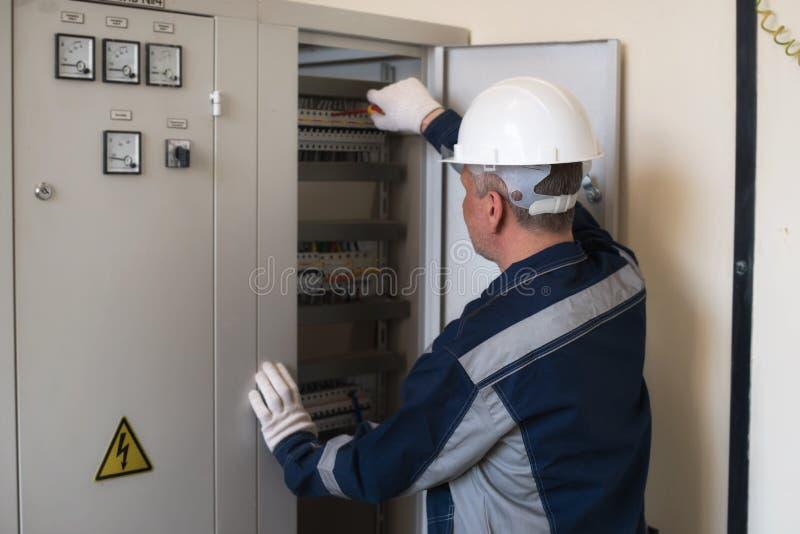 Eletricista do contramestre ao lado do painel Energia e seguran?a el?trica imagens de stock