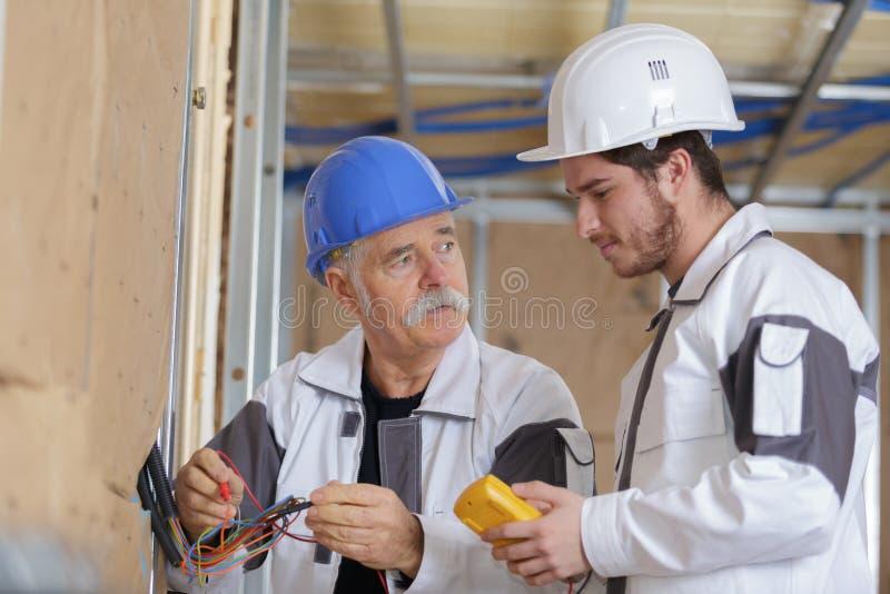 Eletricista dois que verifica a tensão do soquete com o multímetro digital fotografia de stock