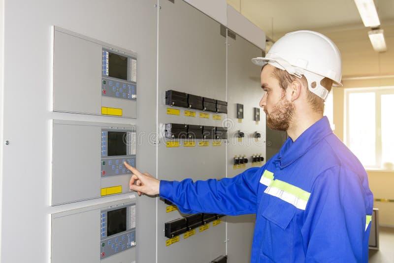 Eletricista Engineer no painel de controlo O trabalhador controla processos industriais imagens de stock royalty free