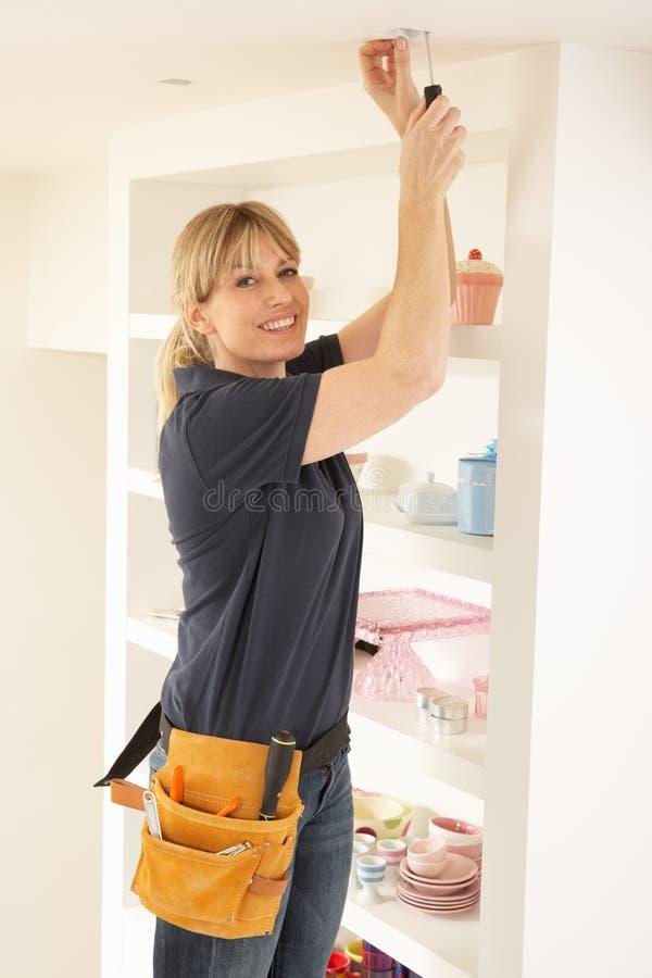 Eletricista fêmea que instala a luz imagens de stock
