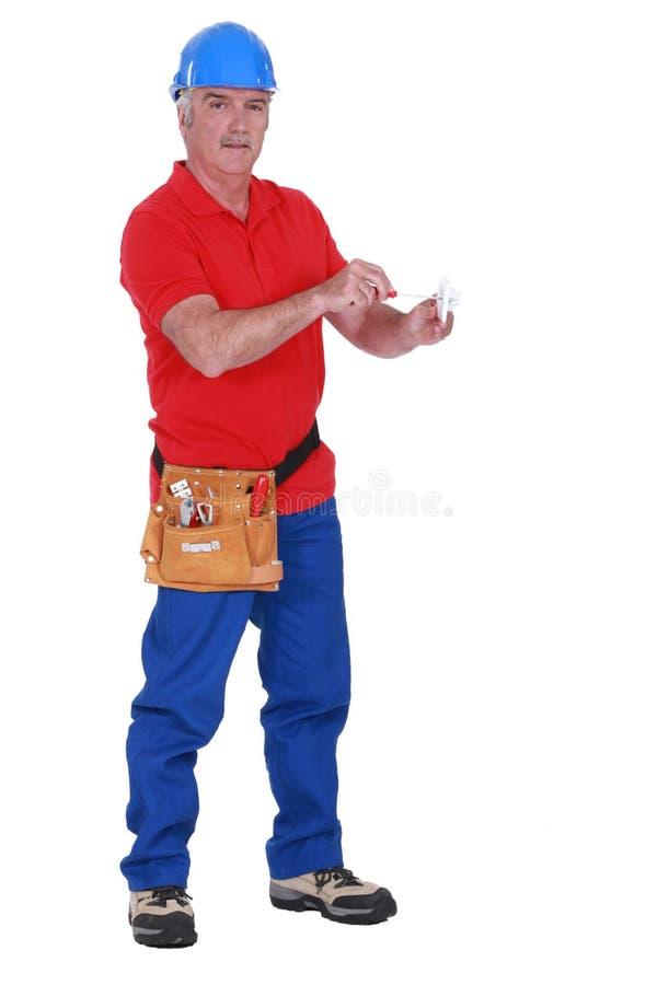 Eletricista maduro que fixa uma tomada. imagens de stock