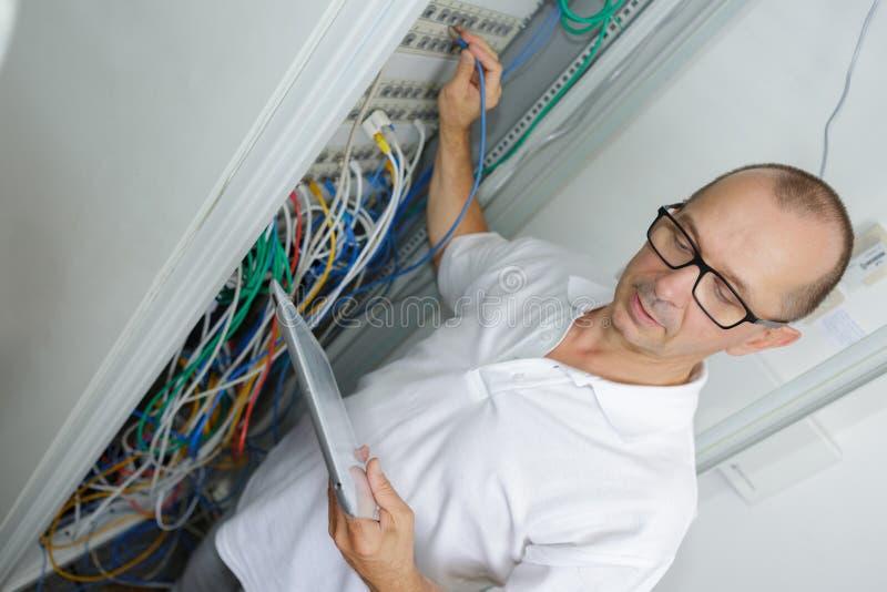 Eletricista na caixa de junção que guarda a tabuleta imagem de stock
