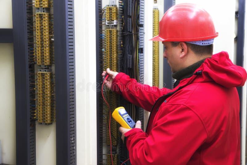 Eletricista no circuito de controle vermelho com multímetro imagens de stock