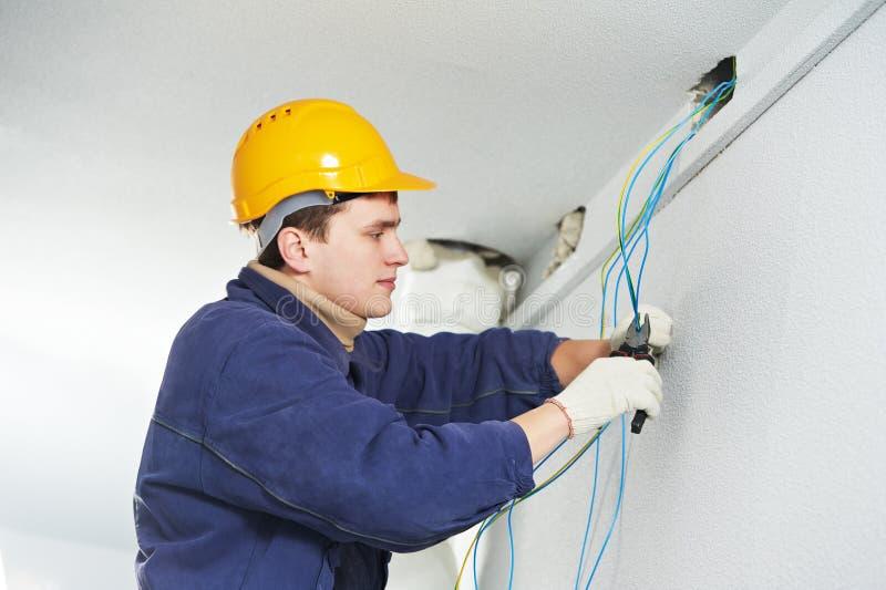 Eletricista no trabalho da fiação do cabo fotografia de stock