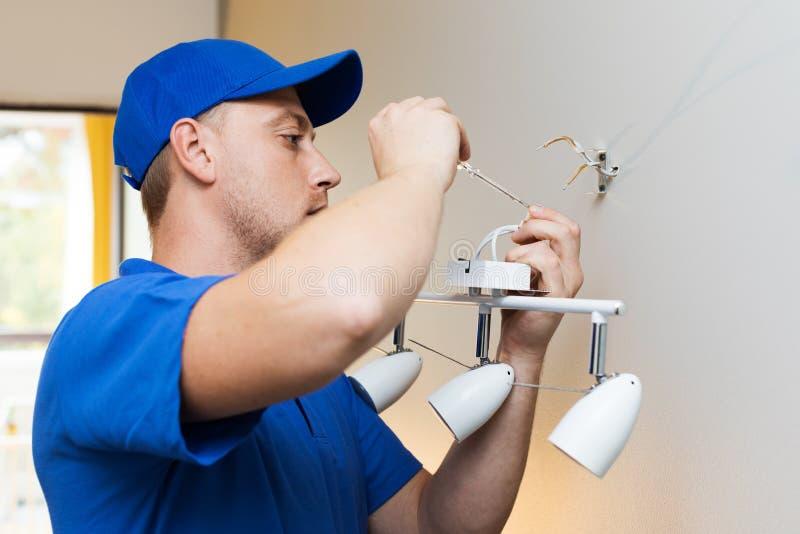 Eletricista no trabalho - instalando a lâmpada na parede foto de stock