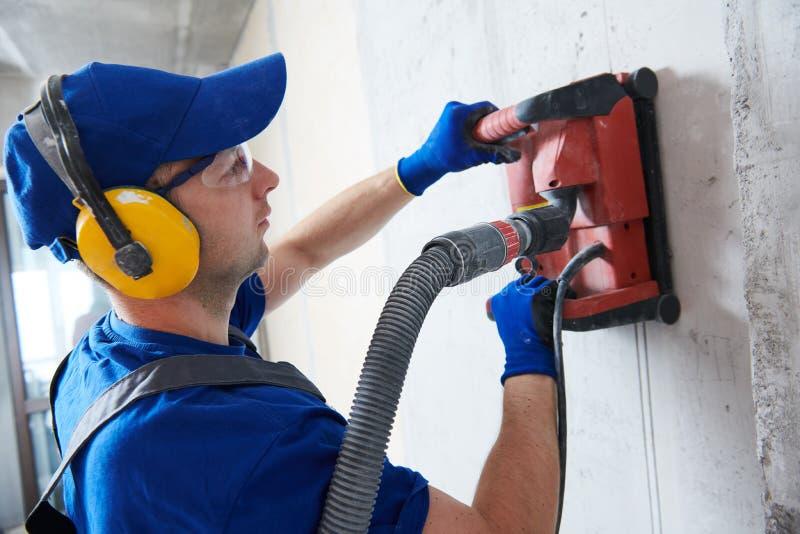 Eletricista no trabalho muro de cimento do corte para cabografar pela máquina de corte do diamante imagem de stock