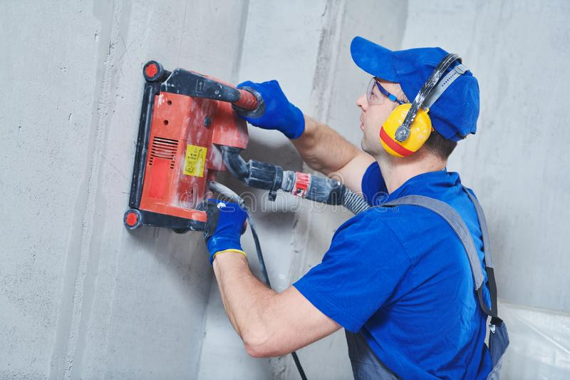 Eletricista no trabalho muro de cimento do corte para cabografar pela máquina de corte do diamante fotos de stock
