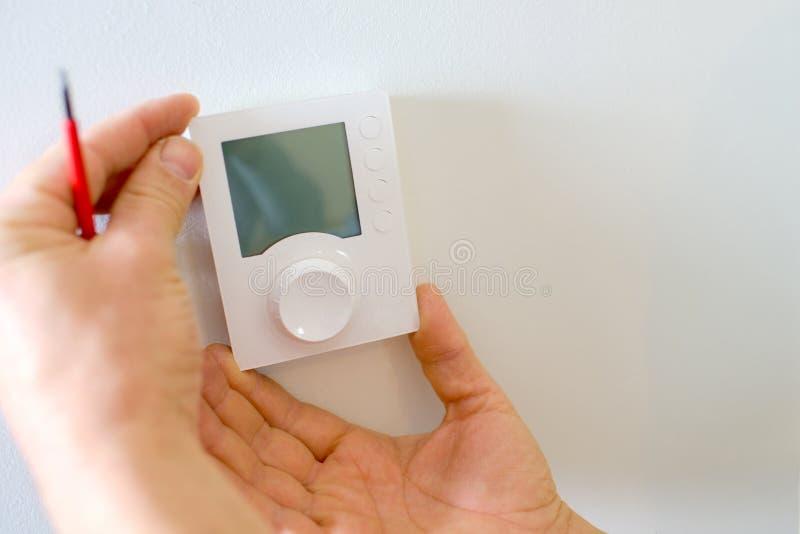 Eletricista que cabe o termostato novo imagem de stock royalty free