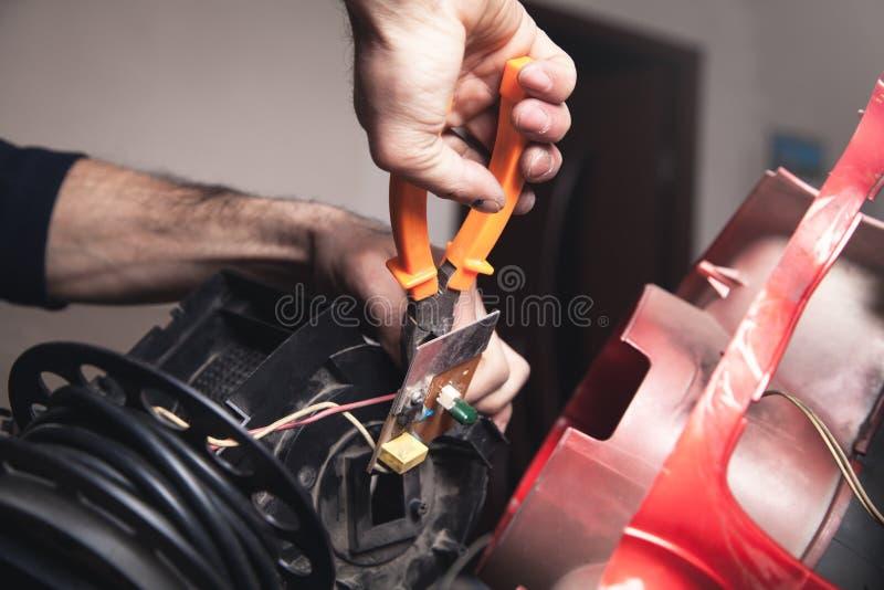 Eletricista que corta o cabo com cortadores fotos de stock royalty free