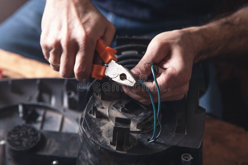 Eletricista que corta o cabo com cortadores imagem de stock royalty free