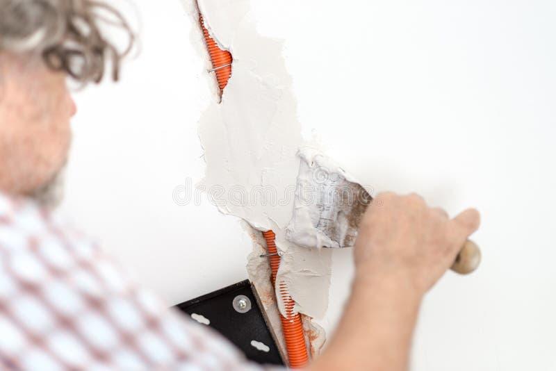 Eletricista que emplastra a fiação recessed em uma parede imagens de stock royalty free