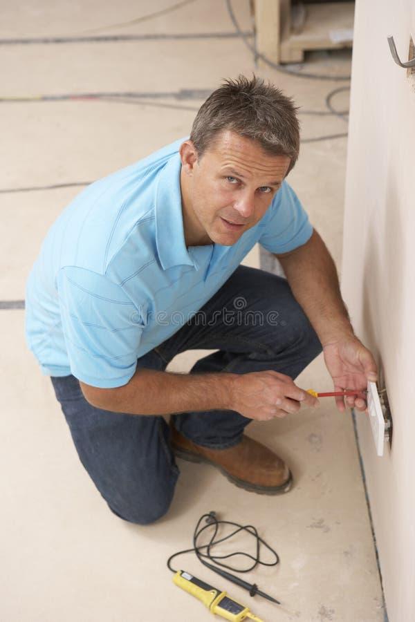 Eletricista que instala o soquete de parede imagens de stock