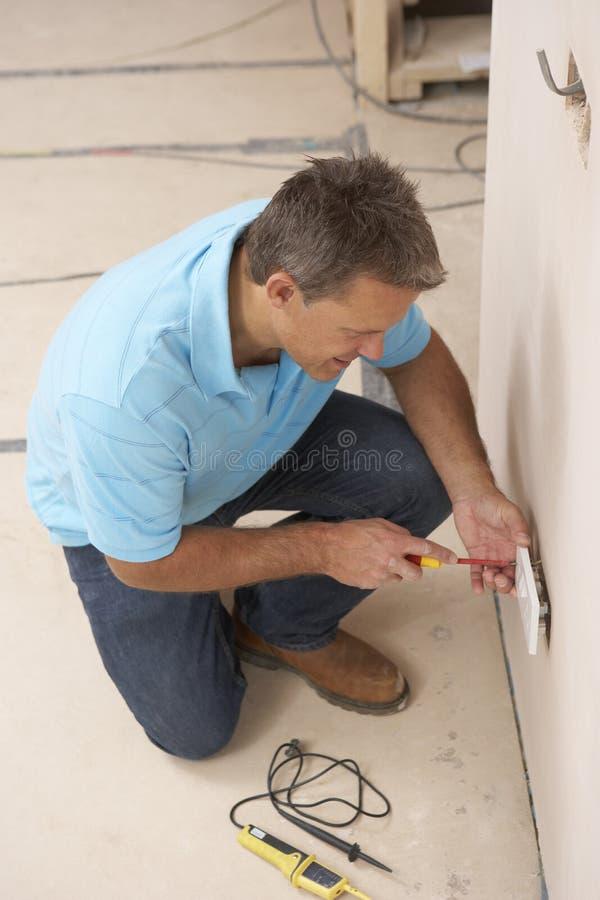 Eletricista que instala o soquete de parede imagem de stock royalty free