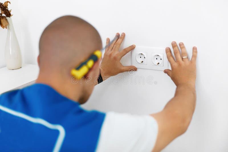 Eletricista que instala o soquete de parede fotografia de stock royalty free