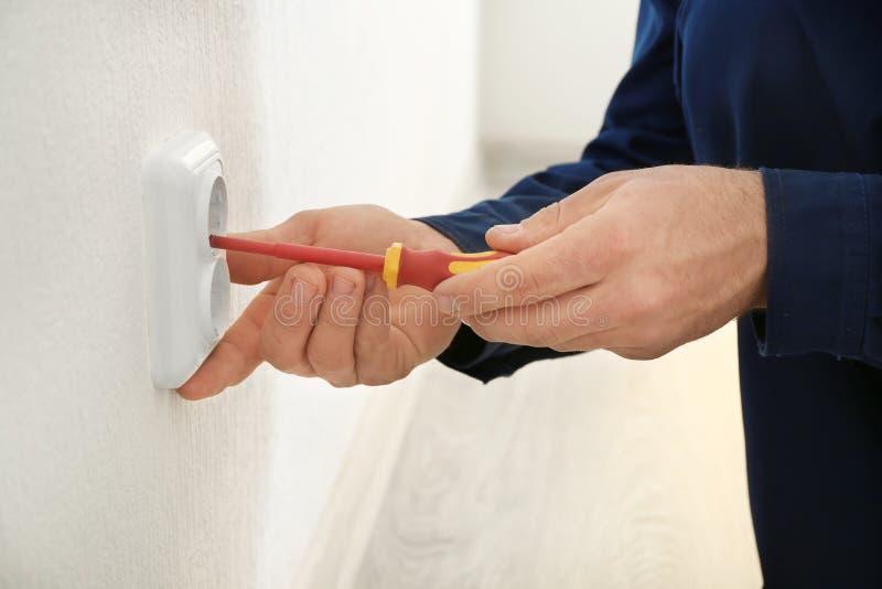 Eletricista que instala o soquete de parede na construção nova, imagem de stock