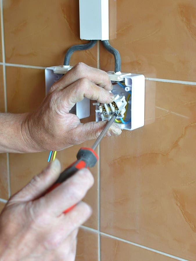 Eletricista que instala o soquete de parede na construção nova, foto de stock