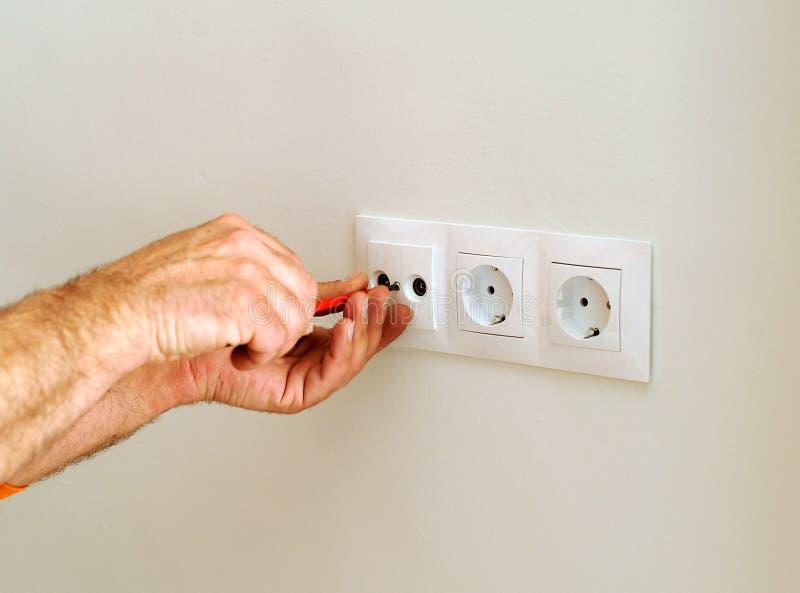 Eletricista que instala os soquetes de poder na casa foto de stock royalty free