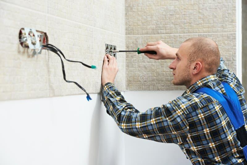 Eletricista que instala tomadas de parede fotografia de stock royalty free