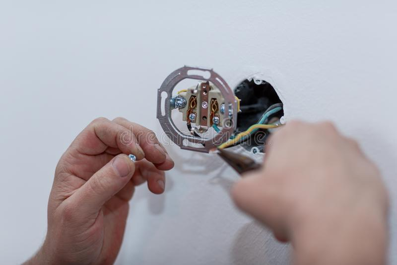 Eletricista que instala um soquete fixado na parede da alimentação CA com um SCR fotografia de stock