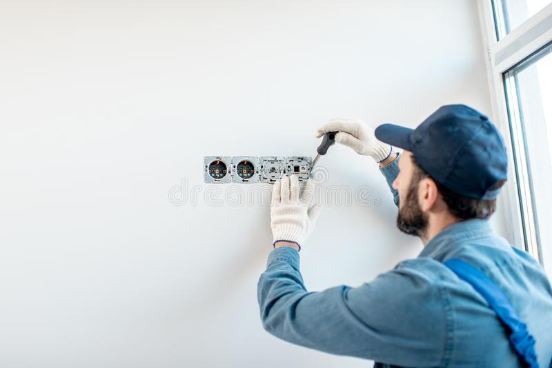 Eletricista que monta os soquetes dentro foto de stock