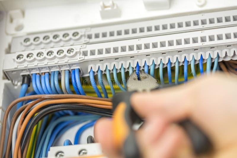Eletricista que repara a fiação defeituosa foto de stock