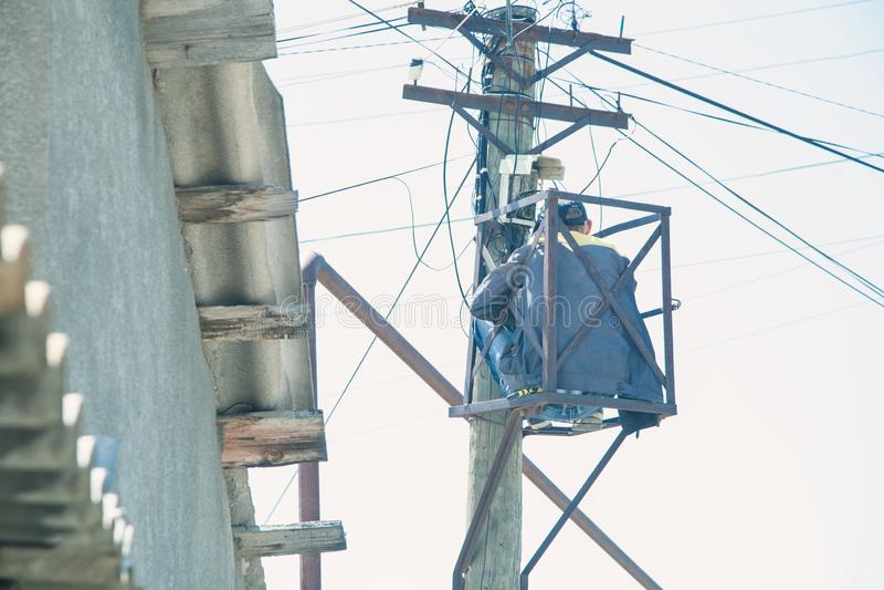 Eletricista que repara o cabo distribuidor de corrente na elevação foto de stock royalty free
