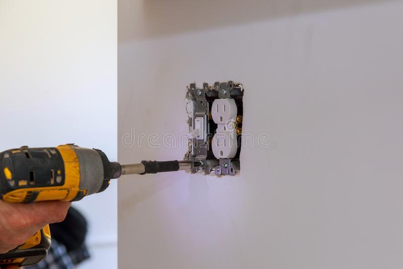 Eletricista que repara o interruptor da parede dentro imagem de stock royalty free