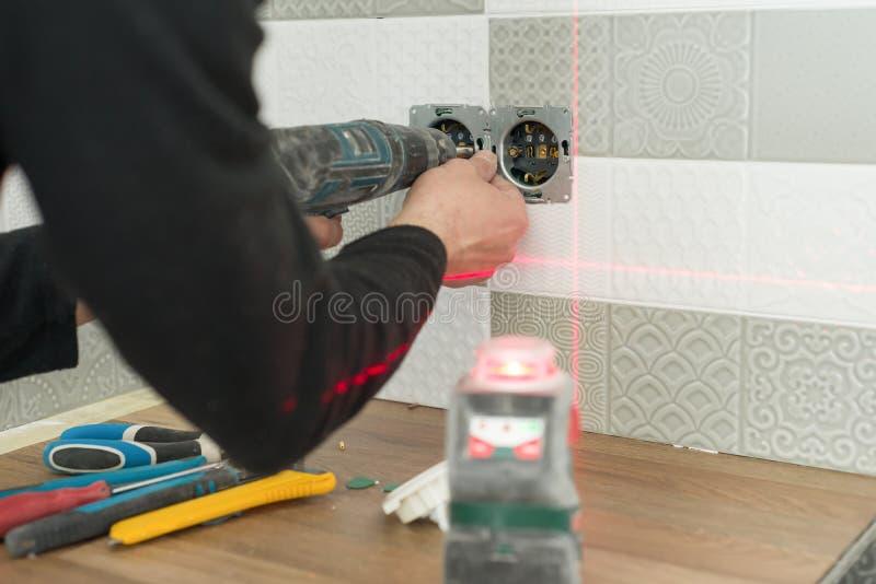 Eletricista que usa o nível infravermelho do laser para instalar tomadas elétricas Renovação e construção na cozinha fotografia de stock royalty free