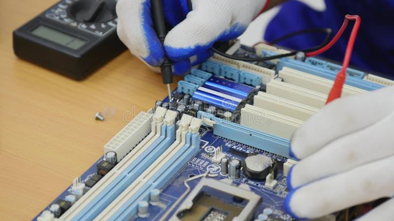 Eletricista que usa o voltímetro para o equipamento de escritório da verificação e do reparo fotos de stock royalty free