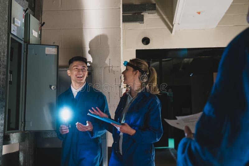 Eletricistas do estagiário no porão fotos de stock