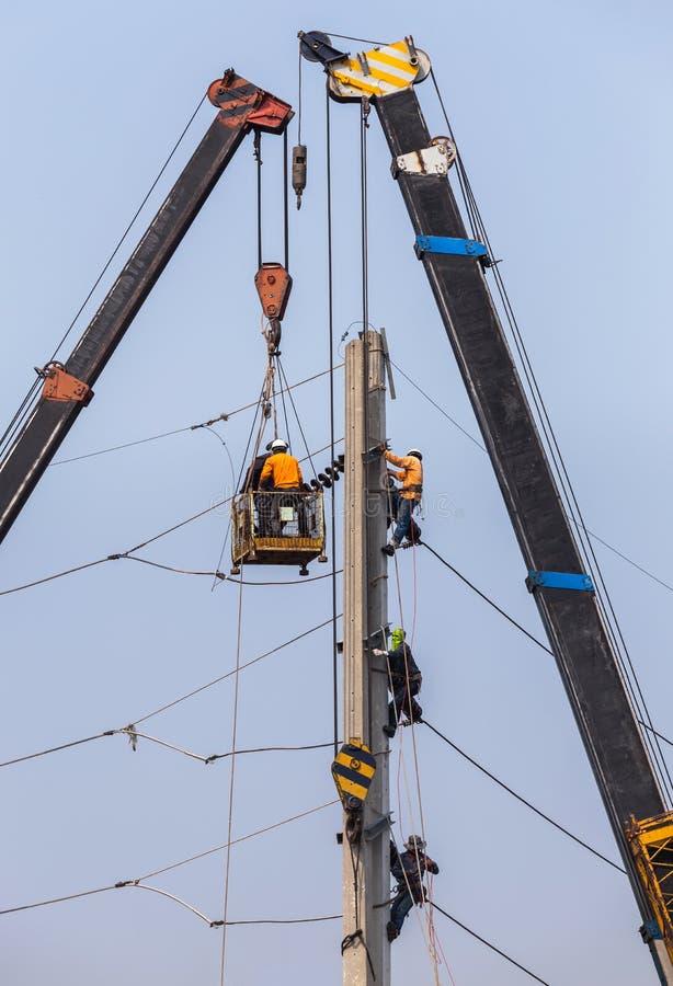 Eletricistas que reparam o fio no polo de poder da eletricidade com plataforma hidráulica fotos de stock