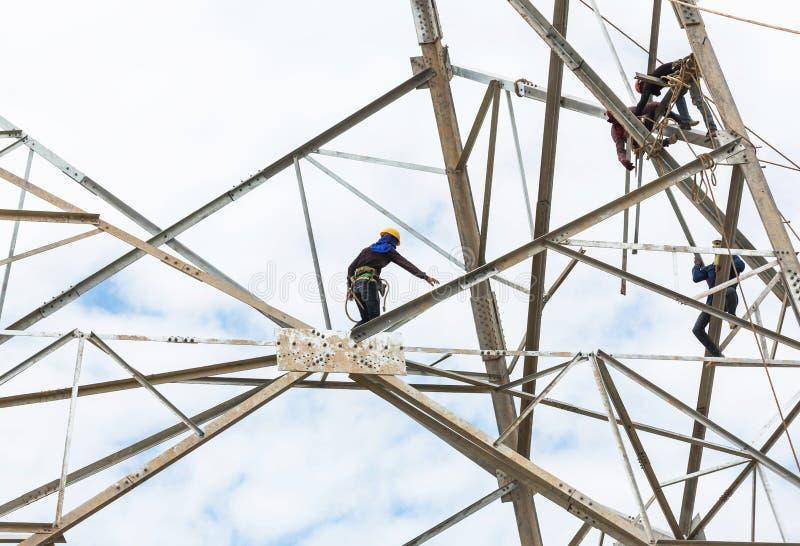 Eletricistas que trabalham na torre da construção do pilão foto de stock